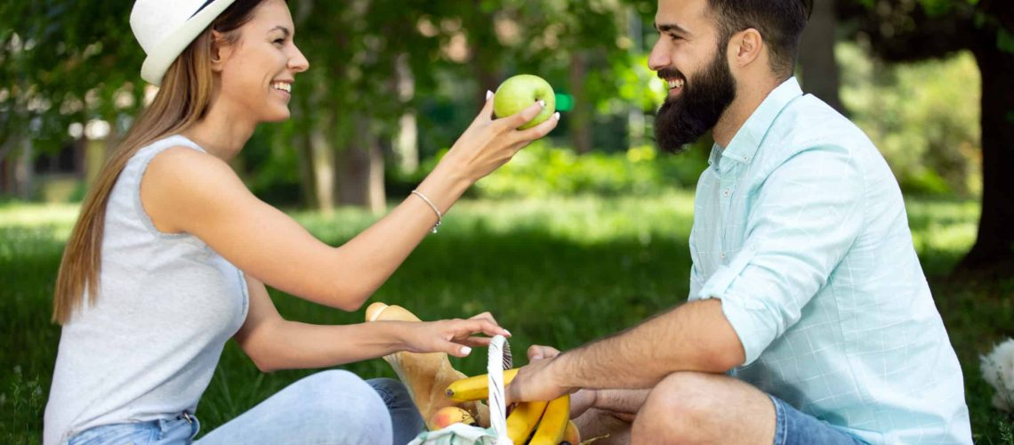 Beautiful young couple enjoying picnic day. Lifestyle, love, dating, vacation concept