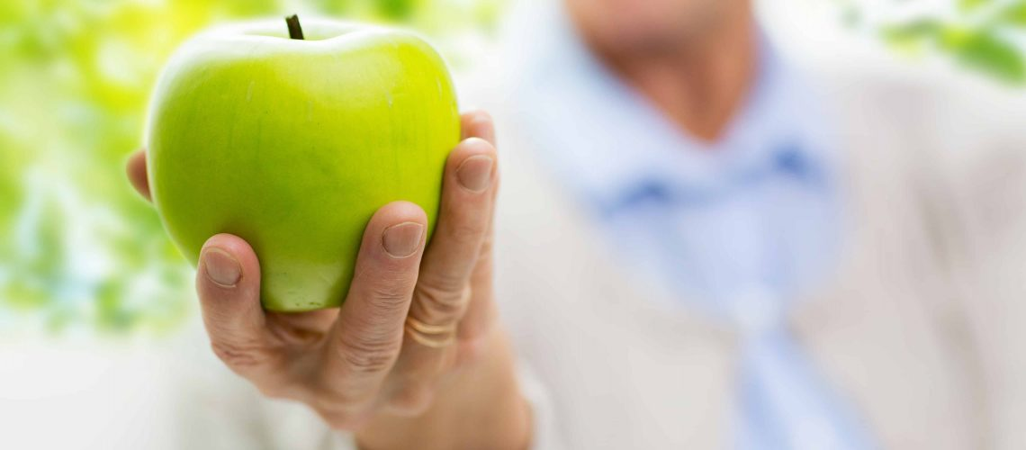 age, healthy eating, food, diet and people concept - close up of happy smiling senior woman with green apple at home