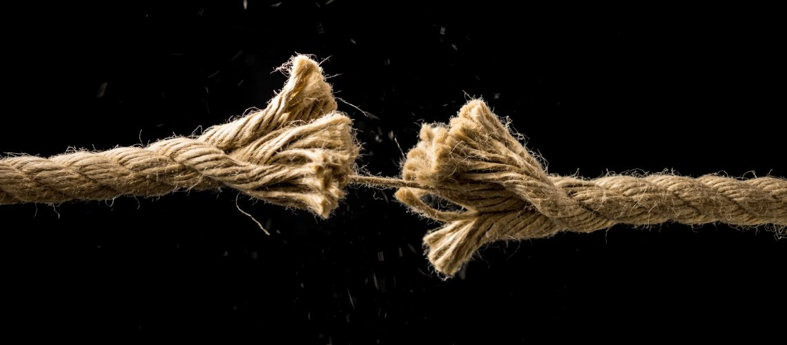 Concept of danger and risk with two ends of a frayed worn rope held together by the last strand on the point of snapping, against a dark background with copyspace.