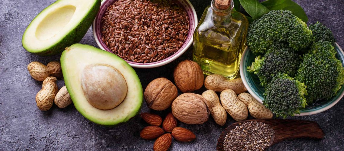 Vegan fat sources – flax, spinach, broccoli, nuts, olive, oil and avocado. Concept of healthy food