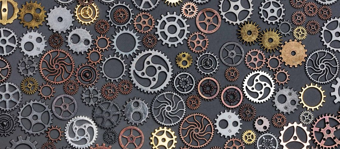 Different cogwheels laying on grey background. Industrial parts. Flat lay.