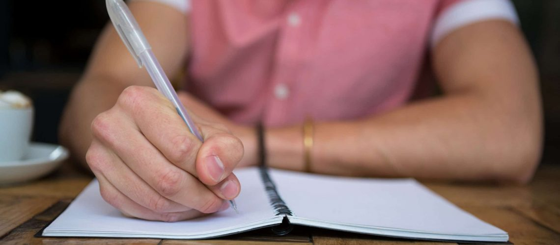 Midsection of man writing in diary at table in coffee shop