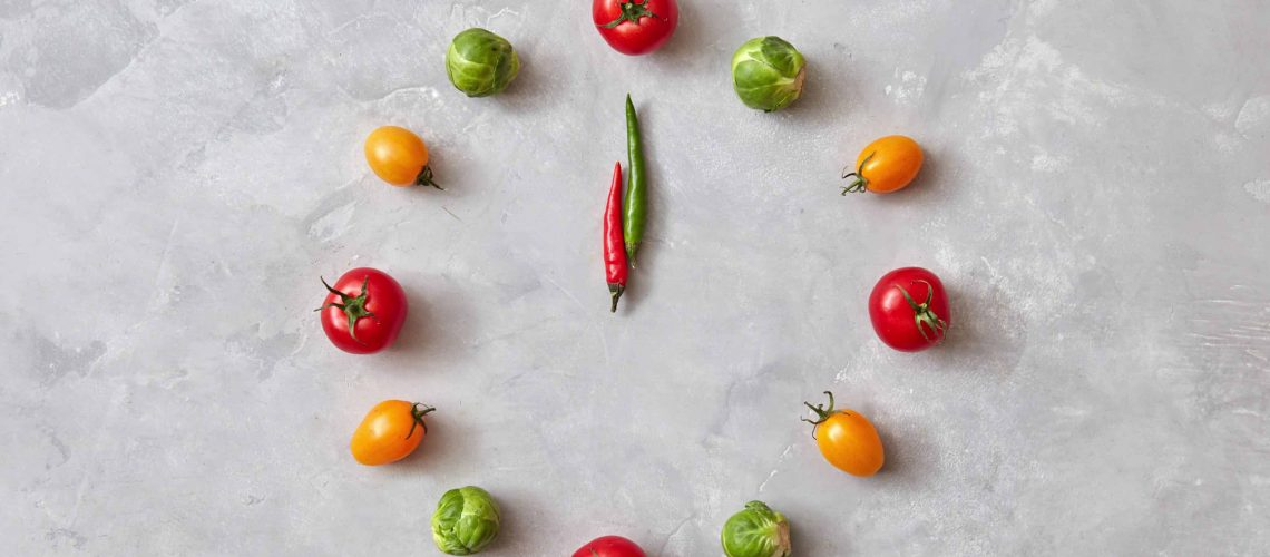 Vegetable clock from colorful cherry tomatoes, carrots, brussels cabbage and moving arrows from chili peppers on a gray stone background. Flat lay.