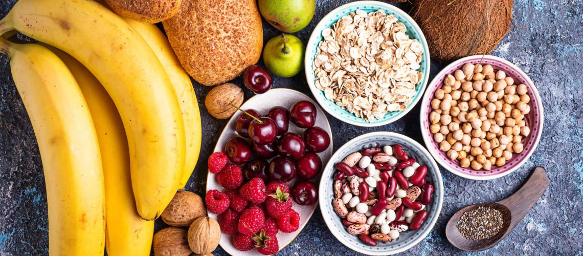Products rich in fiber. Healthy diet food. Fruits, beans, berries, bread, oatmeal, chia and nuts. Top view