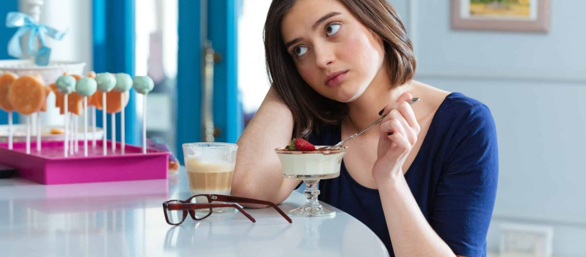 Sad tired young woman eating dessert and drinking latte at bar counter in cafe