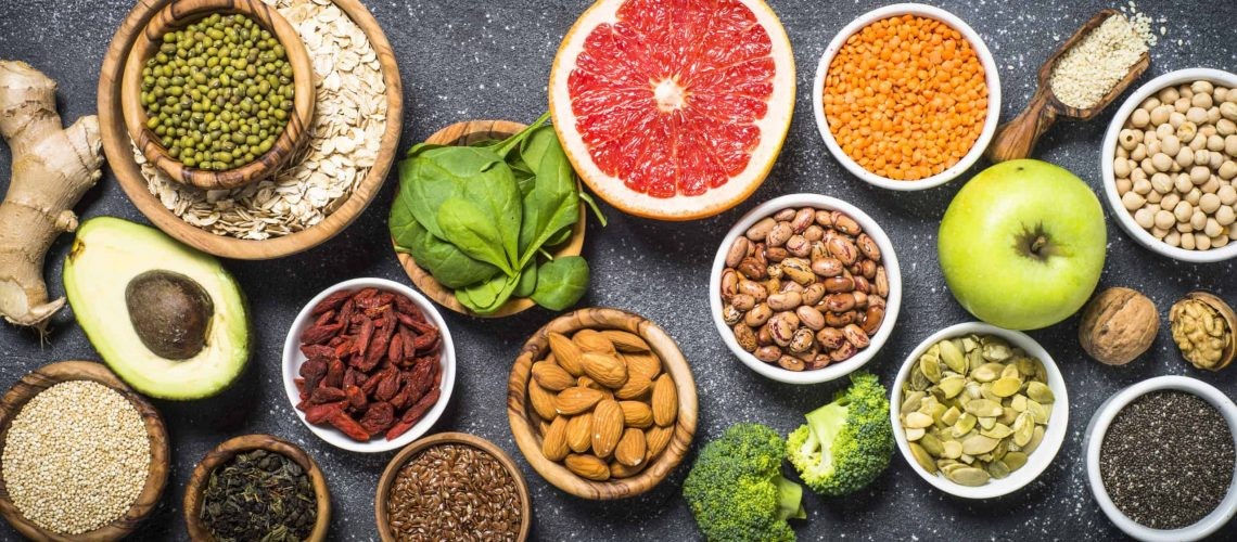 Superfoods on black stone background. Legumes, nuts, chia, avocado, grapefruit, beans, goji, green apple and asparagus and quinoa. Top view.