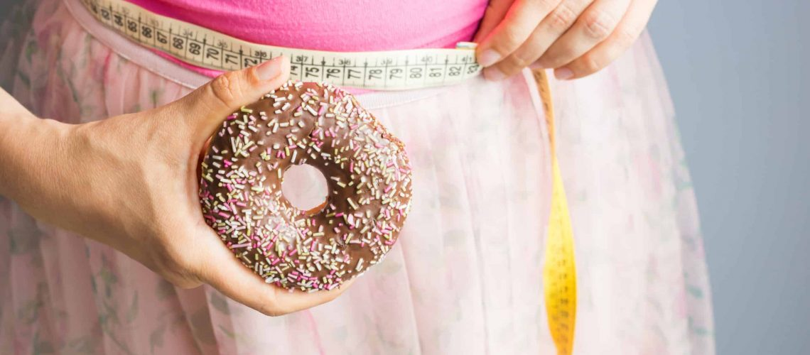 Woman holding donut in hand and check out his body fat with measuring tape